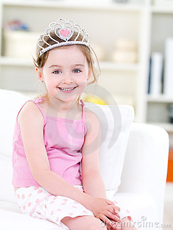 Little happy girl with crown at home