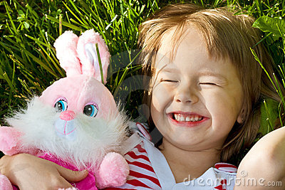 Little happy girl lies in grass