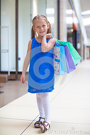 Little happy girl with packages in a large