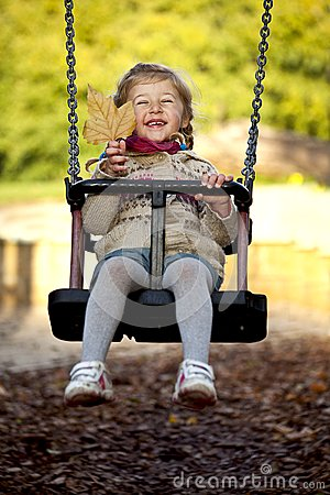 Little happy girl on the swing