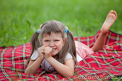 Little irritated girl preschooler lying on plaid