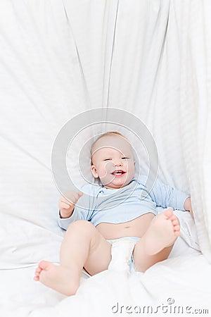 Little joyful baby fall on bed