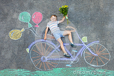 Little kid boy having fun with bicycle chalks picture on ground Stock Photo