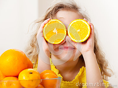 Little kid with oranges
