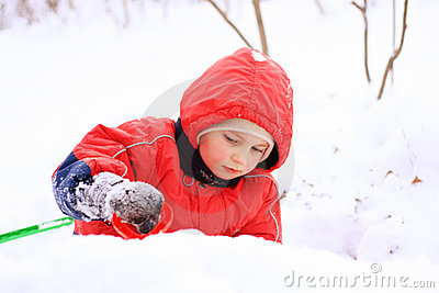 Little kid in red jacket playing in snow