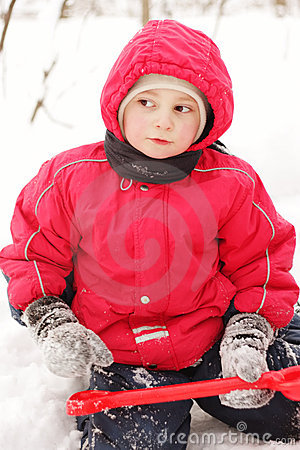 Little kid in red jacket sitting with shovel