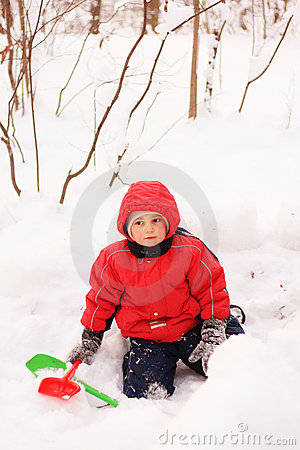 Little kid in red jacket sitting on snow
