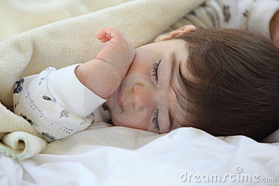 Little kid sleep on bed.