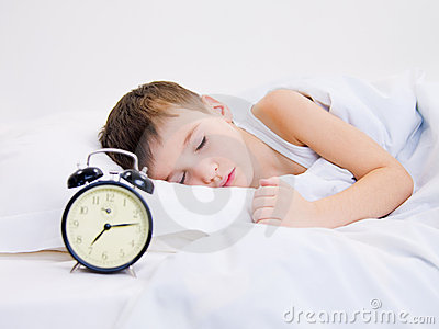 Little kid sleeping with  clock near his head