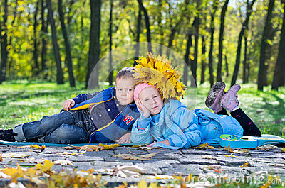 Little kids lying close together in an autumn park