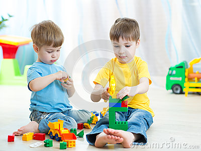 Little kids play with building bricks in preschool