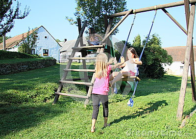 Little kids - girls playing on swing