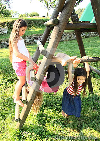 Little kids - girls playing on wooden construction