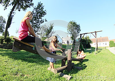 Little kids playing on wooden swing