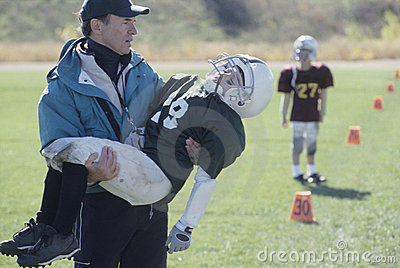 Little League coach with injured football player