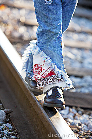 Little legs and feet walking on railroad track