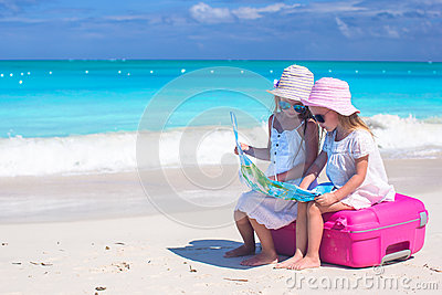 Little lovely girls sitting on big suitcase and a map at tropical beach