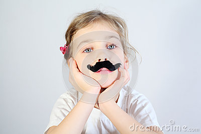 Little melancholy girl with glued fake mustache.