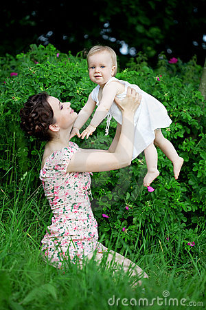Little pretty baby on a green lawn with mom