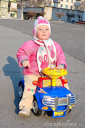 Little pretty girl sit on the toy car.