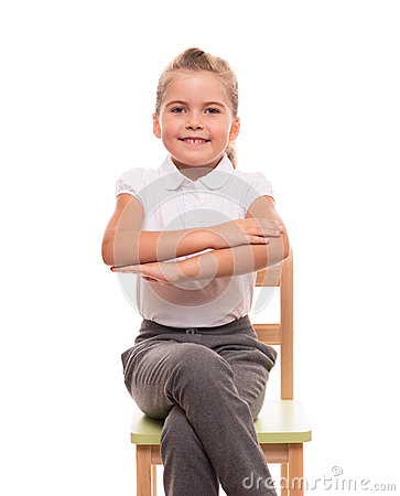 Little schoolgirl sitting on a chair and holding her hands in fr