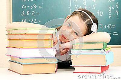 Little schoolgirl sleep in classroom