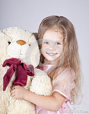 Little shouting girl embraces bear cub.