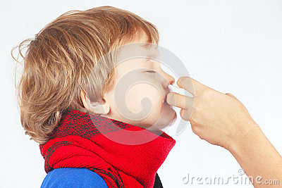 Little sick boy used nasal spray in the nose