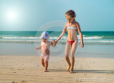 Little sisters walking along the beach