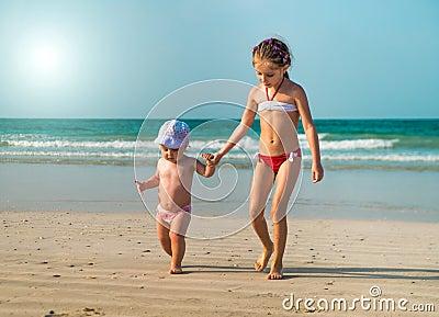 Little sisters walking along the beach