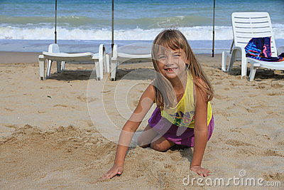 Little six-year-girl playing in the sand on the beach.