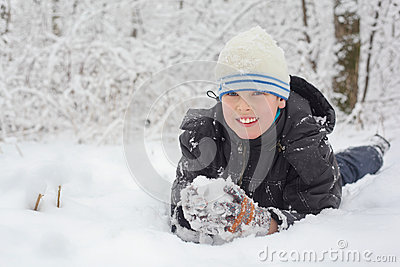 Little smile boy lie on snow