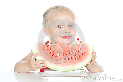 Little smiling blonde girl eating a watermelon