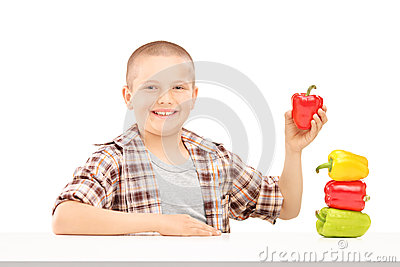 A little smiling boy holding colorful peppers on a table
