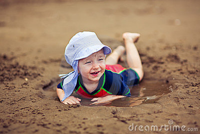Little smiling boy in the mud puddle
