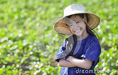 Little smiling girl farmer on green fields