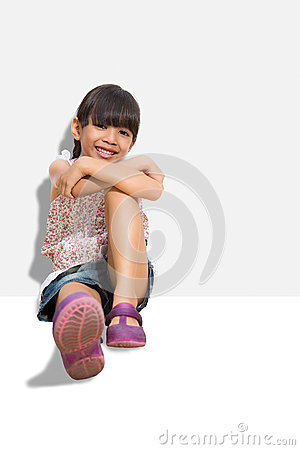 Little smiling girl sitting on the ground