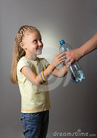 Free Little Smiling Girl Takes Water Bottle From Hands Of An Adult On Gray Stock Photo - 111577300