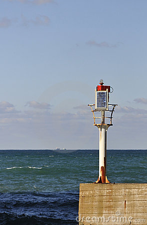 Little solar lighthouse on a concrete jetty