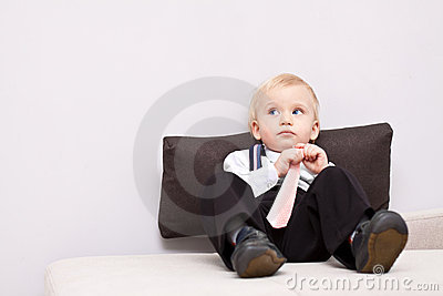 Little tired businessman sitting on the sofa