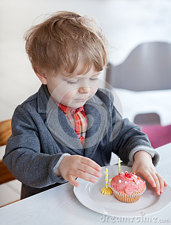 Little toddler blowing two birthday candles