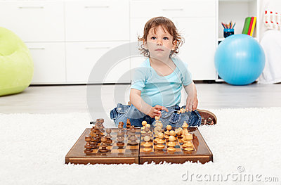 Little toddler boy with chess board
