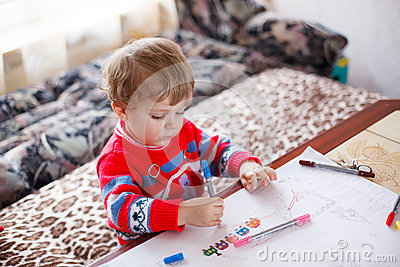 Little toddler boy drawing with colorful pens