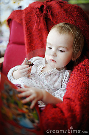 Little toddler girl eating chocolate