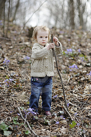 Little toddler girl playing with a stick