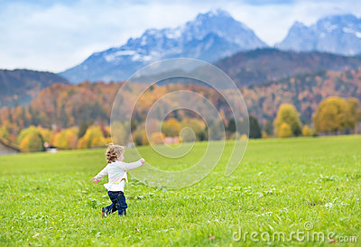 Little toddler girl running in a beautiful field between snow co