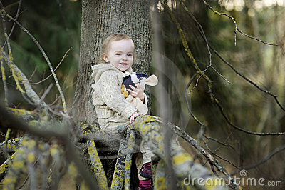 Little toddler girl sitting at a tree branch