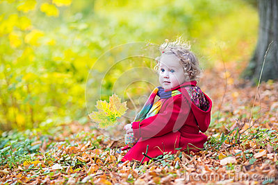 Little toddler girl wearing red in autumn park coat