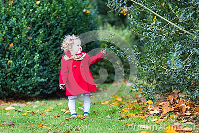 Little toddler girl wearing a red coat in autumn park