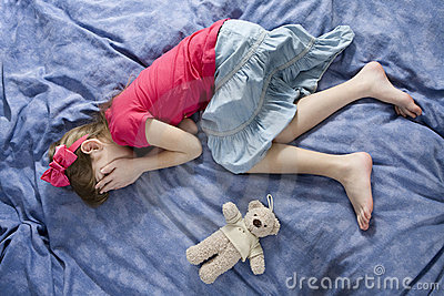 little upset crying girl lying on the bed stock images